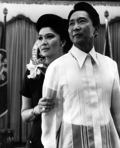 President Marcos and First Lady Imelda stand before the president's desk and seal in Malacañang Palace. Marcos wears a Pierre Cardin Barong Tagalog.