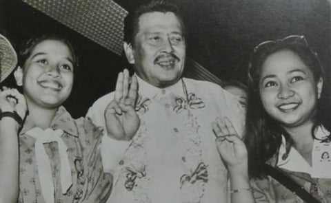 Estrada poses for pictures with Girl Scouts. He wears a barong, and this pic is likely from the late 1990's.