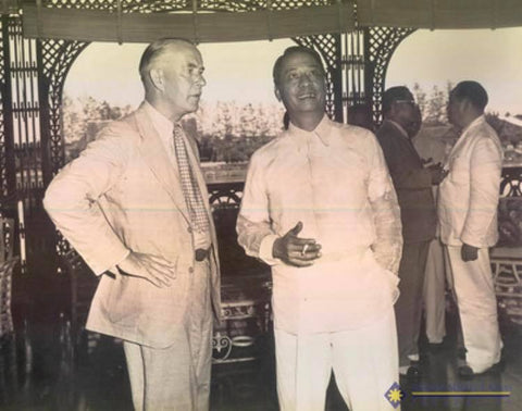 Manuel Roxas smokes a cigarette and converses with an American dignitary in his Barong Tagalog