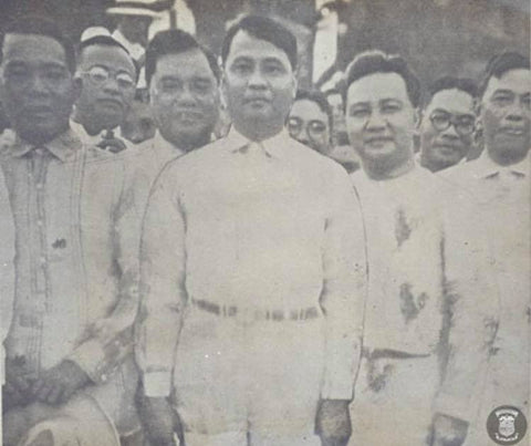 Manuel Roxas is in the center wearing a Barong Tagalog. To the right of him is Elpidio Quirino. This photo is from 1933