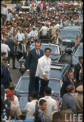 Marcos in a barong stands on a limousine with US President Richard Nixon during his 1969 visit to the Philippines.