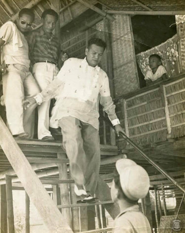 Magsaysay walks down the stairs after meeting at a constituent's home. He wears a barong.