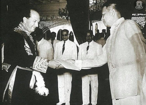 President Magsaysay meets with and receives the credentials of an ambassador in the ceremonial room of Malacañang Palace. He wears a Barong Tagalog.