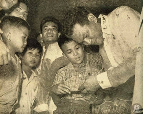 President Magsaysay meets with a crowd of boys on Christmas in his barong