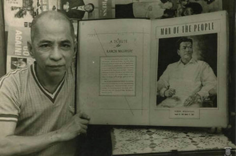 A man holds a book open to a tribute to President Magsaysay and the famous painting of him in a Barong Tagalog.