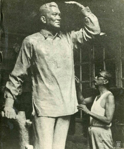 Sculptor works on a statue of President Magsaysay in a Barong Tagalog.