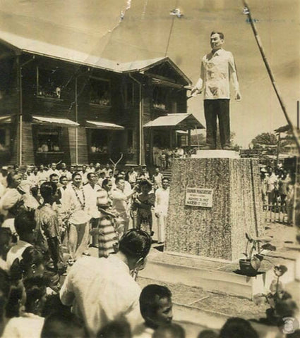 Townspeople gather around a statue of President Magsaysay in a Barong Tagalog.