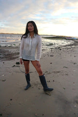 Andrelie standing in her custom hand embroidered jusi Barong Tagalog, black shorts and black boots on the sand with her hand on her leg and the water behind her at Dead Horse Bay Beach in Brooklyn, NY