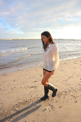 Andrelie walking in her custom hand embroidered jusi Barong Tagalog, black shorts and black boots on the sand next to the water at Dead Horse Bay Beach in Brooklyn, NY