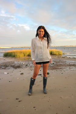 Andrelie standing in her custom hand embroidered jusi Barong Tagalog, black shorts and black boots on the sand with tall grass and water behind her at Dead Horse Bay Beach in Brooklyn, NY