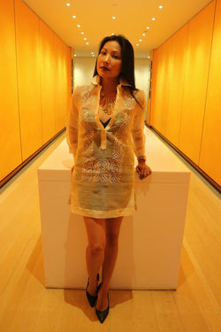 Anna stands and leans with hands resting on white table behind her in orange hallway. Anna wears a dress length hand embroidered piña silk Barong Tagalog