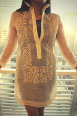 Product picture of dress length hand embroidered piña silk Barong Tagalog with bars and window behind her