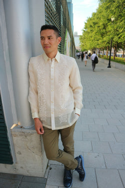 Arland stands and leans on grey pillar in his long sleeve full button down hand embroidered piña silk Barong Tagalog, olive green pants and black shoes. There are people walking and trees behind Arland in the distance. Arland is at the Jersey City Waterfront