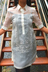 Product picture of the dress length hand embroidered cocoon Bianca Barong Tagalog with red stairs behind her