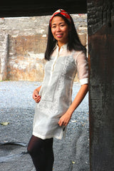 Bianca stands, smiles and leans on dark wood pillar in her hand embroidered cocoon Barong Tagalog, with black leggings and red and white headband with a stone wall in the background