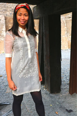 Bianca stands smiling in her dress length hand embroidered cocoon Barong Tagalog, black leggings and red and white headband next to dark wooden pillars and a stone wall behind her.
