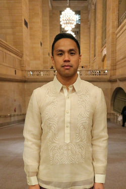 Photo from waist up of Blase in his hand embroidered piña silk Barong Tagalog  in Grand Central Terminal in NYC with beige walls and chandelier behind him