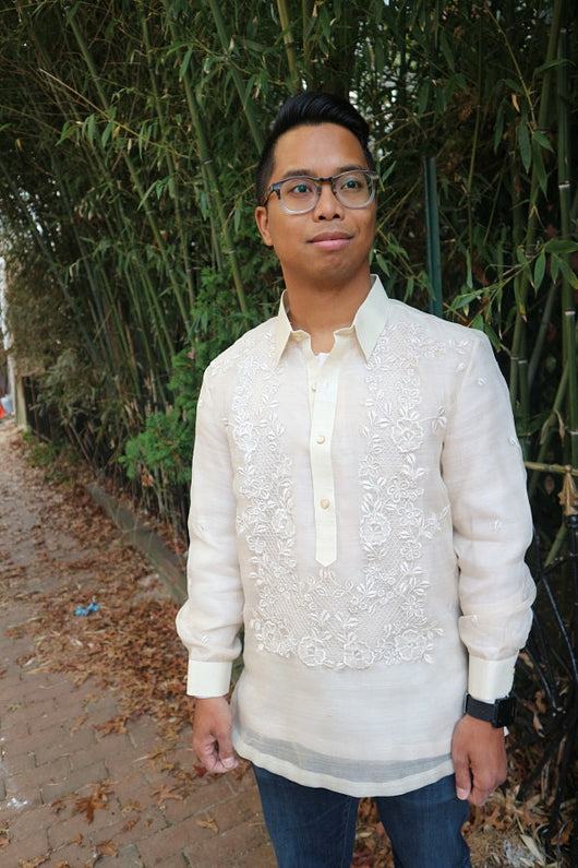 Shot of Bryan from his thighs up wearing his hand embroidered piña silk Barong Tagalog, blue jeans, black watch and glasses. Bryan stands on a brick walkway with dead leaves on the ground and bamboo branches and leaves behind him