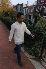Bryan walks towards a wrought iron black gate with his left hand extended towards it. Bryan wears a hand embroidered piña silk Barong Tagalog, blue jeans, dark brown shoes, black watch and glasses. Also pictured is the sidewalk, shrubs, trees and a row of houses in the background
