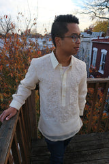 Bryan stands on a wooden deck terrace with his right hand on the wood railing, left hand in his pocket, looking to his left. Bryan wears a hand embroidered piña silk Barong Tagalog, blue jeans and glasses. There are tree top branches, leaves and the tops of houses behind him