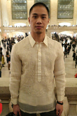 Chris pictured from the waist up with his hands at his sides. Chris wears his hand embroidered piña silk Barong Tagalog, dark pants and black bracelet. Behind Chris is Grand Central Terminal in NYC with crowds of people standing and walking