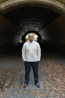 Chris U stands in front of a tunnel in Prospect Park, Brooklyn, with his hands in his pockets wearing his hand embroidered jusi Barong Tagalog, blue slacks and brown dress shoes