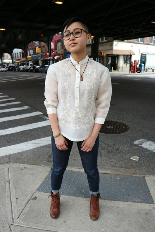Chrissi stands at the corner of 69 Street and Roosevelt Avenue in Little Manila in Woodside, NY. Chrissi wears a hand embroidered jusi Barong Tagalog, blue jeans, brown boots, glasses and a necklace.