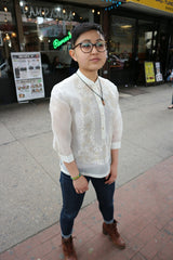 Angled shot of Chrissi wearing a hand embroidered jusi Barong Tagalog, blue jeans, brown boots, glasses and a necklace while standing on the sidewalk in front of Renee's restaurant in Little Manila in Woodside, NY