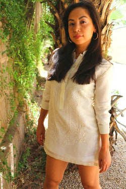 Coley from the knees up wearing a dress length hand embroidered cocoon Barong Tagalog next to a wall with green vines and leaves hanging off of it and a palm tree trunk behind her