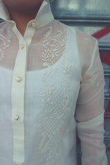 Product shot of Dom's left shoulder and chest area of her hand embroidered cocoon Barong Tagalog. The center button placket shows, the collar is standing up, and the left arm and sleeve shows also
