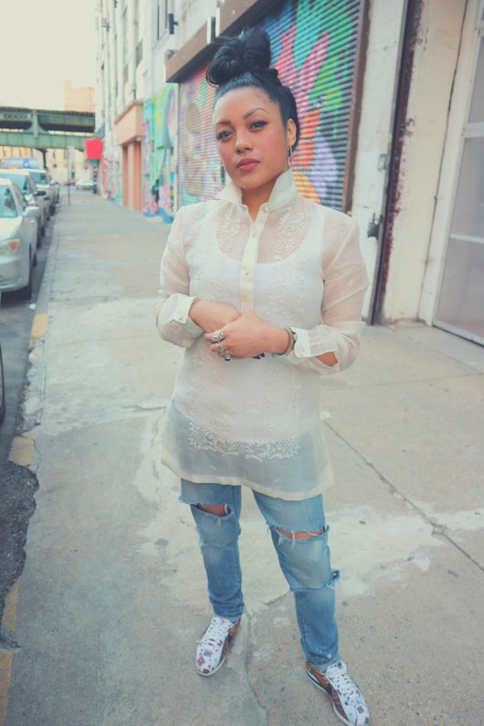 Dom stands on the sidewalk wearing a dress length hand embroidered cocoon Barong Tagalog with ripped blue jeans, multicolored Nike Cortez's, bracelets, rings and earrings with her hair in a bun on top of her head. Dom stands holding her hands in front of her with buildings and colorful murals behind her