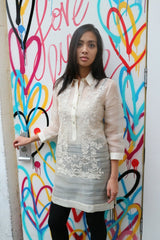 Iris Z stands before a white door with multi-color hearts spray painted on it. She has her right hand on the door handle and left hand at her side. Iris Z wears a dress length hand embroidered piña silk Barong Tagalog, with beige tank camisole and black leggings underneath.