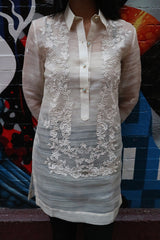 Product picture of the dress length Iris Z hand embroidered piña silk Barong Tagalog. Model has her hands behind her back and stands before a multi-colored mural