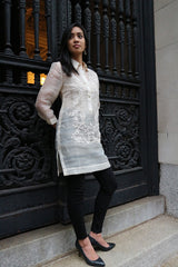 Angled full body picture of Iris Z standing with her back to black cast iron decorative gates. Iris stands with her hands behind her back and looking to her right. She wears a dress length hand embroidered piña silk Barong Tagalog, with beige camisole, black leggings and black high heeled shoes underneath