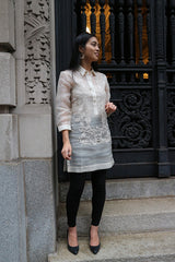 Front full body picture of Iris Z standing on stairs in front of a black cast iron decorative gate and a carved stone wall to her right. Iris stands with her left hand lifted next to her waist, right hand down at her side and looking to her left. She wears a dress length hand embroidered piña silk Barong Tagalog, with beige camisole, black leggings and black shoes underneath