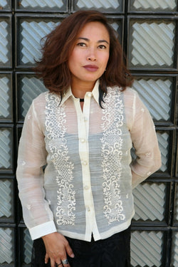 Iris B wears a full button down hand embroidered piña silk Barong Tagalog with black dress underneath. Iris stands in front of a wall with textured tiles
