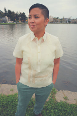 Irma stands in front of Lake Merritt with her hands in her pockets and she looks away. Irma wears a jusi short sleeve Barong Tagalog and green khaki pants. The lake and homes are in the background.