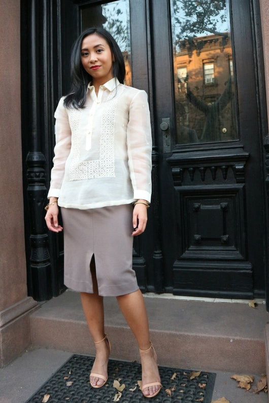 Jenny stands in front of black doors with windows reflecting the brick building across the street. Jenny wears a hand embroidered piña silk Barong Tagalog, grey skirt and pink open toe shoes