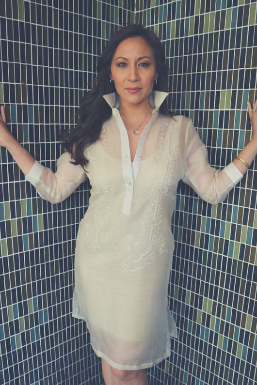 Jeri stands in the corner of two multicolor tile walls with her hands resting on the wall. Jeri wears her dress length hand embroidered cocoon Barong Tagalog, a beige minidress underneath her barong, hoop earrings, heart pendant necklace, gold bangles and diamond ring on her left arm and hand