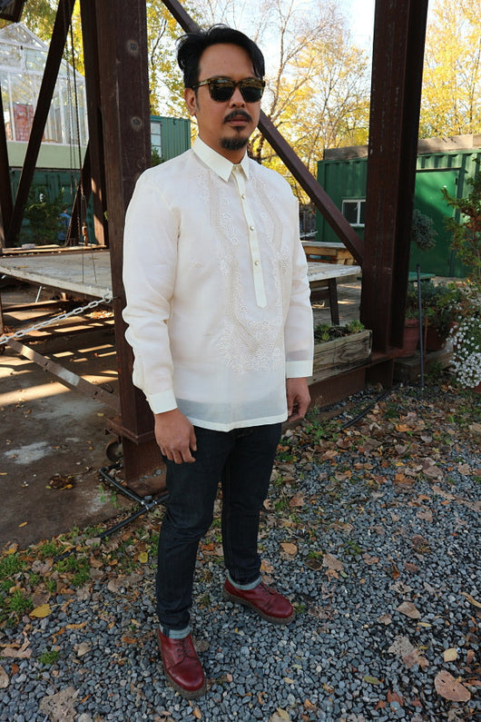 Angled shot of John-T standing on a gravel walkway in front of a wooden table and steel beams. John-T wears a hand embroidered jusi Barong Tagalog, dark sunglasses, dark blue jeans and dark red Doc Marten boots. There are trees and green buildings in the background