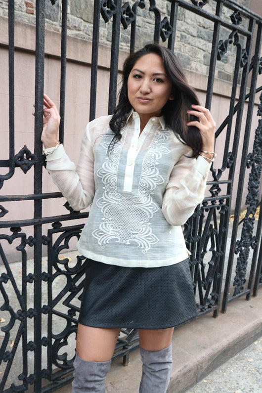 Kristina stands next to a black iron gate and touches one of the bars with her right hand. Her left hand holds and brushes her hair. Kristina wears a hand embroidered piña silk Barong Tagalog, black tank top underneath barong, black perforated leather miniskirt, gold bracelets on each wrist and you can see only the tops of her suede lavendar thigh high boots