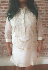 Product shot of the hand embroidered jusi Krystal Barong Tagalog. There is wood flooring, white base boards and a brick wall in the background