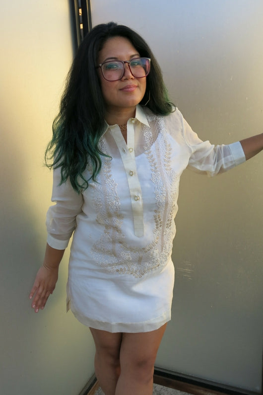 Krystal wearing a dress length hand embroidered jusi Barong Tagalog. She stands between 2 panels of frosted glass. She wears plastic rimmed glasses.