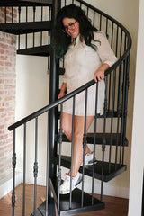 Krystal walks down a spiral staircase in her dress length hand embroidered jusi Barong Tagalog. She holds onto the bannister and is wearing Air Jordan 3 White Cement sneakers and plastic rimmed glasses