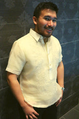 Angled photo of Lakhi standing in his hand embroidered cocoon Barong Tagalog. Lakhi also wears black jeans and a silver wrist watch. His hands are by his front pockets, and he stands with his back to a dark grey wall with an all-over print design