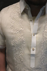 Closeup shot of the right shoulder of the hand embroidered cocoon Lakhi Barong Tagalog. The barong's pointed collar and center button placket is also seen