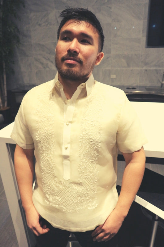 Lakhi stands in his hand embroidered cocoon Barong Tagalog with his black jeans. he stands in front of a white table and chairs with a marble wall in the background