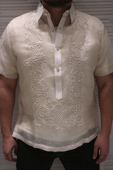Product shot of the hand embroidered cocoon Lakhi Barong Tagalog with short sleeves. Lakhi wears black jeans. His hands are to his side. There is an off-white textured well behind him.