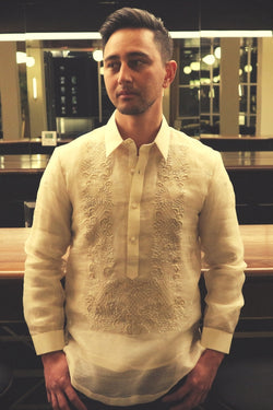 Half body photo of Mansour standing in his hand embroidered piña silk Barong Tagalog. Mansour stands in front of a bar and mirrors. His hands are over his front jeans pockets.