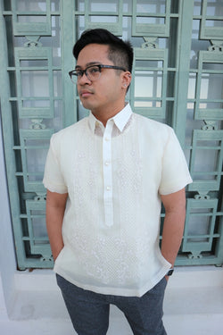 Marc standing in his short sleeve hand embroidered cocoon Barong Tagalog. He also wears grey pants, glasses and a wrist watch. He stands in front of a green decorative window at the Griffith Observatory. He has his hands in his pockets and his head is angled to his right